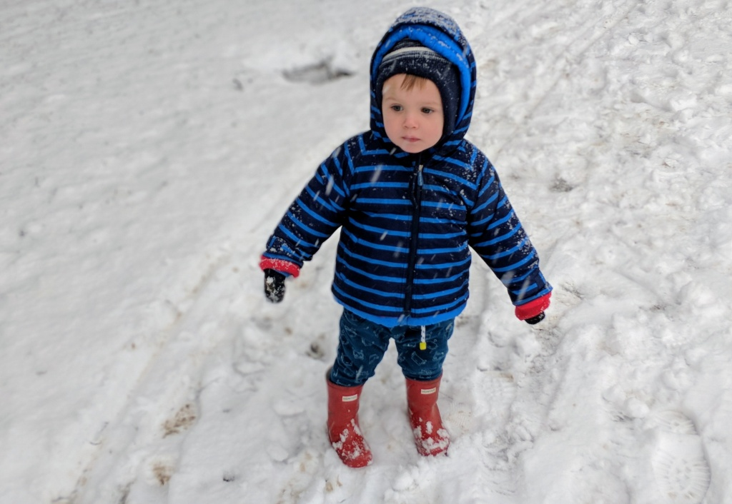 little boy wrapped up warm stood in snow