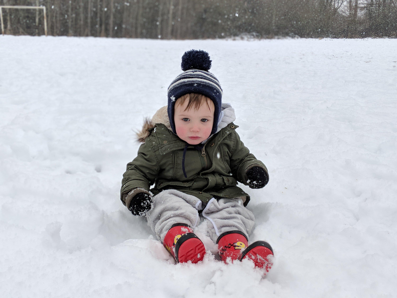 little boy sat in snow