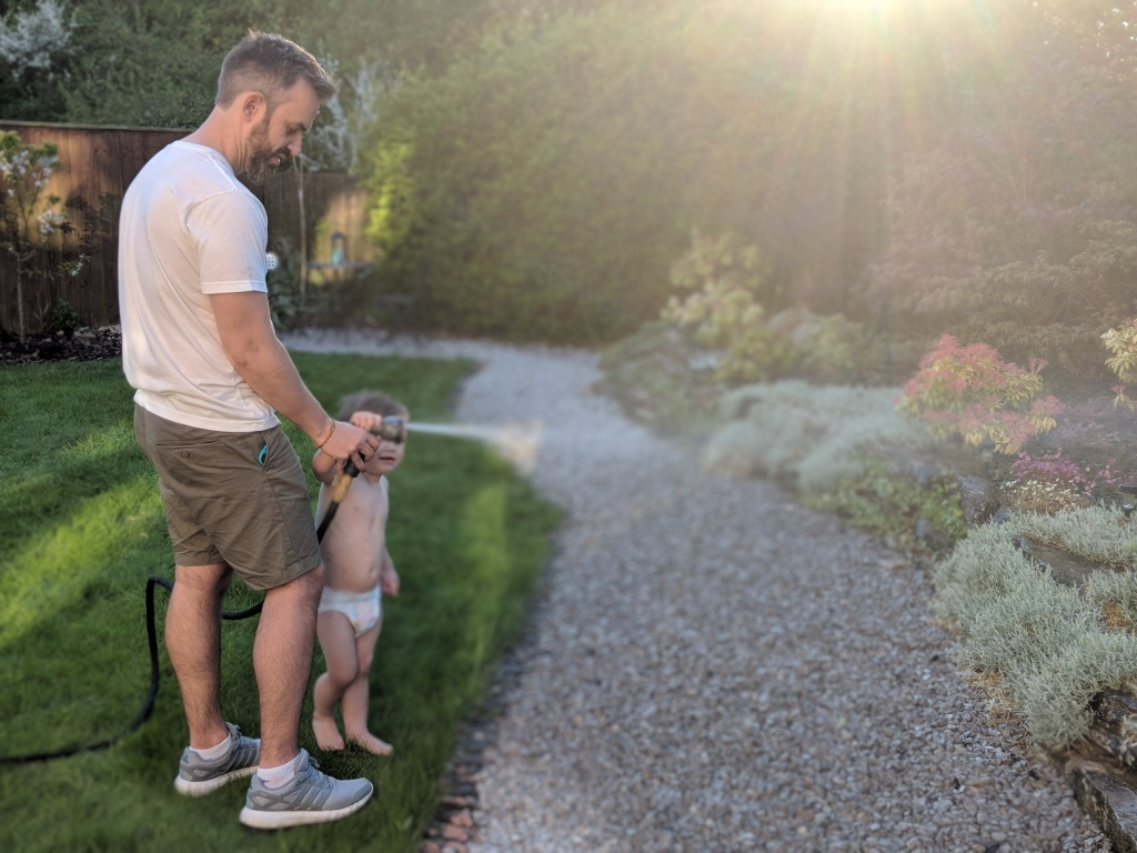 little boy watering garden with hose helped by dad