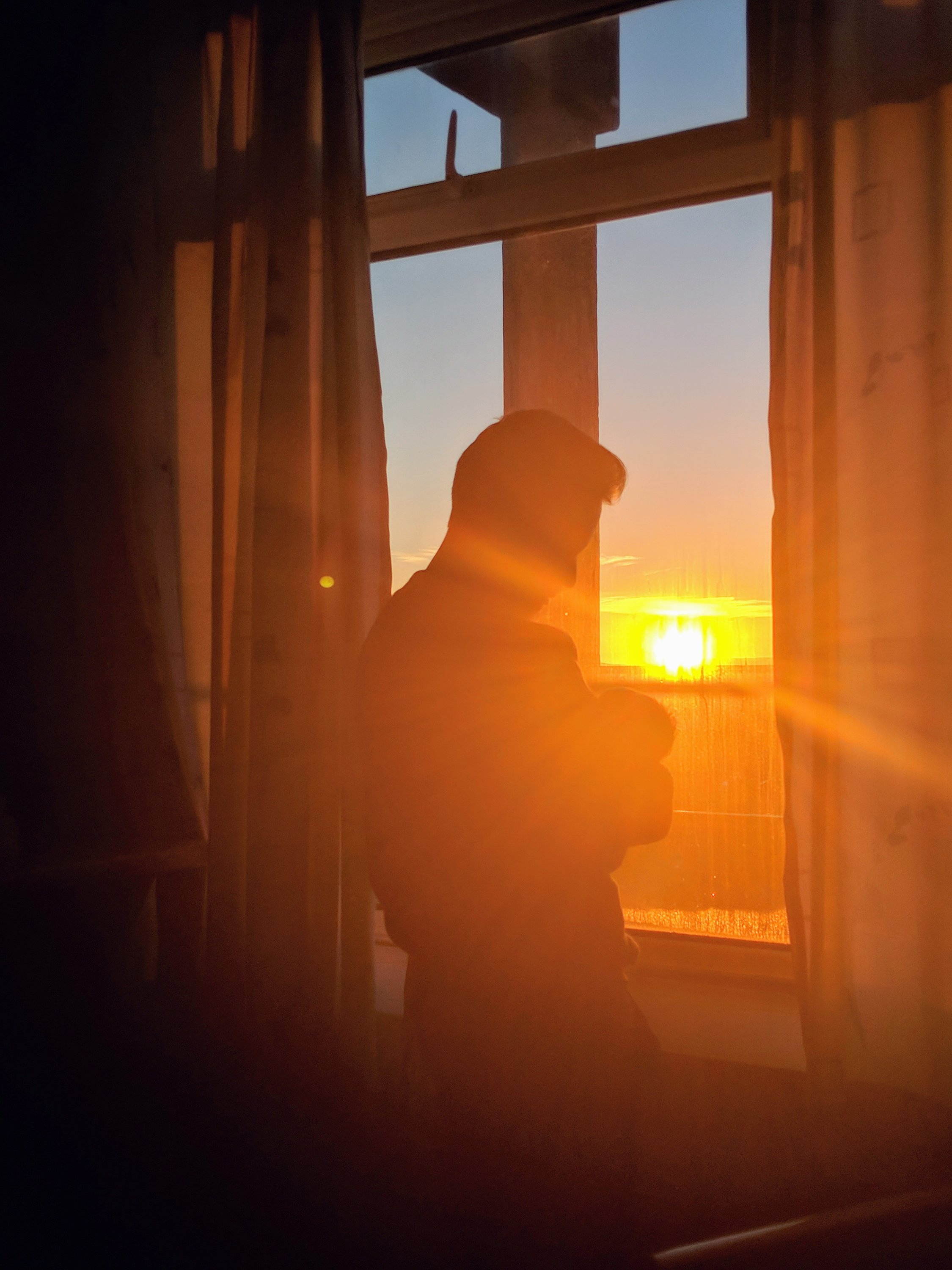 dad holding newborn baby looking at sunrise in darlington memorial hospital