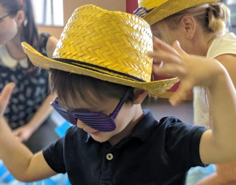 little boy in hat and glasses at a hartbeeps class
