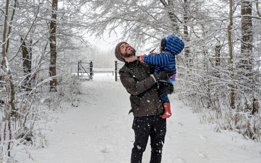 dad holding son in snow at hardwick park sedgefield