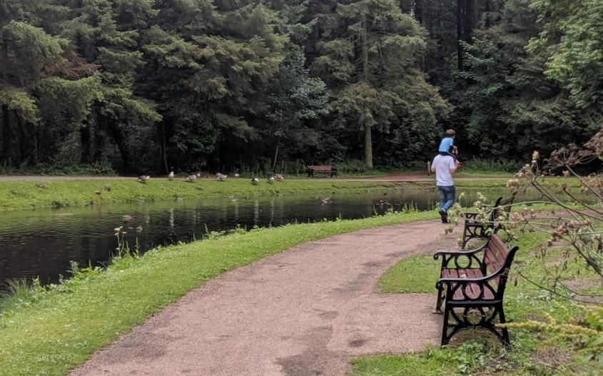 dad with son on shoulders walking past the pond at hardwick park sedgefield