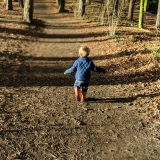 back of little boy running on mud track in hardwick park sedgefield