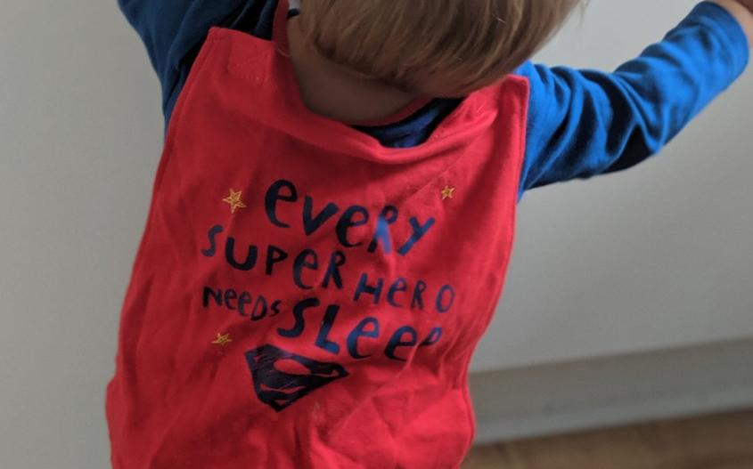 baby stood by cupboard with superman cape on