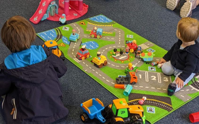 boys sat playing at kalma hub playgroup with cars